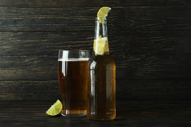 木製の背景にライムとビール