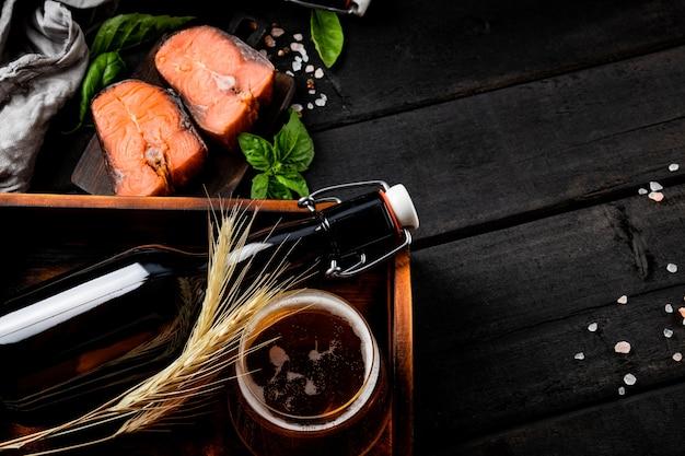Пиво с соленой красной рыбой на черном деревянном фоне. фото высокого качества