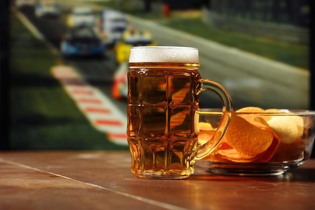 Пиво с закусками на столе на фоне гонки формула-1, концепция спорта и развлечений