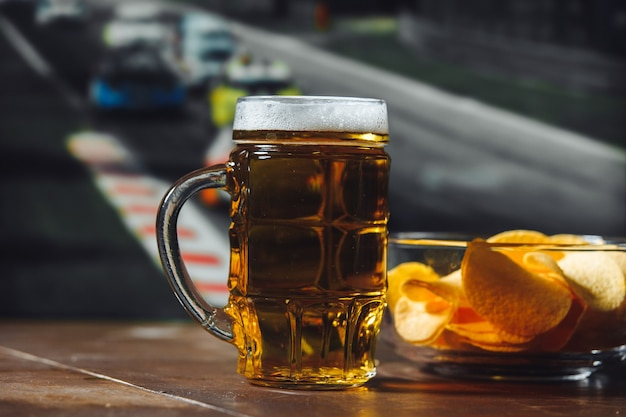 Beer with snack on a wooden table against formula one race background sport and entertainment concept
