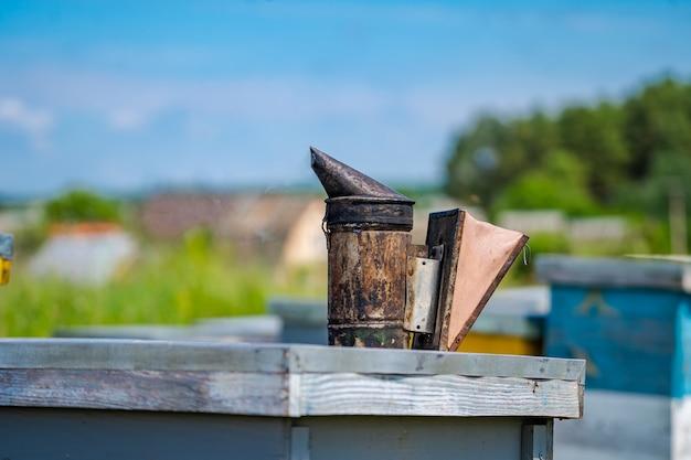 Beesmoker는 다채로운 벌집에 서 있습니다. 꿀과 꿀벌. 푸른 하늘 배경입니다.
