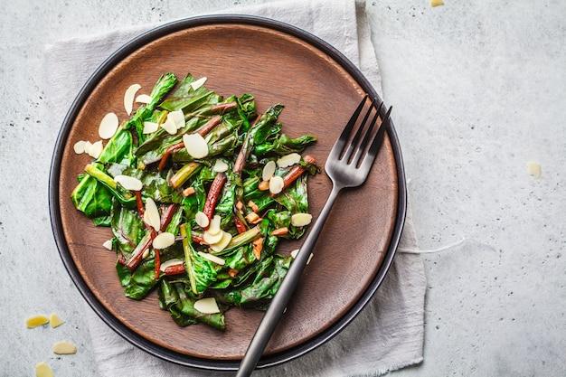 Салат из зелени свеклы с орехами в черной тарелке, концепция здорового веганского питания.