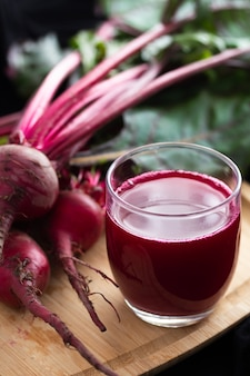 Beet juice in a glass on a wood board, with fresh beets in the
