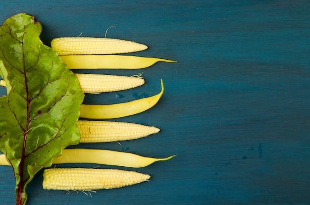 Beet leaf fresh raw corn under the bright wooden surface.