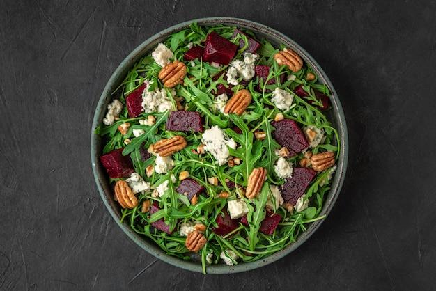 검은 색 표면에 접시에 신선한 arugula, 블루 치즈, 피칸 너트와 비트 또는 비트 뿌리 샐러드