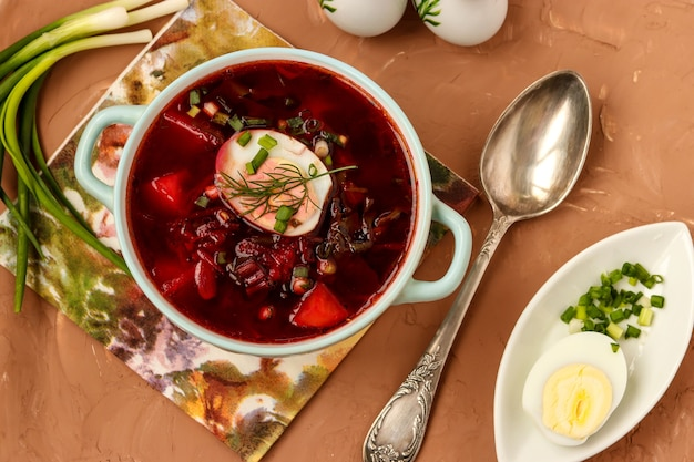 Beet soup in the plate is located on the table, concept is healthy eating, closeup, horizontal orientation, top view
