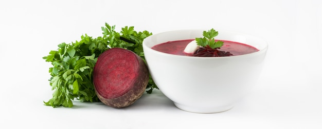 Beet soup in white bowl isolated