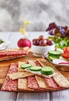 Крекеры из свекольной и ржаной муки с овощами для приготовления закусок на деревянной стене. вегетарианство и здоровое питание