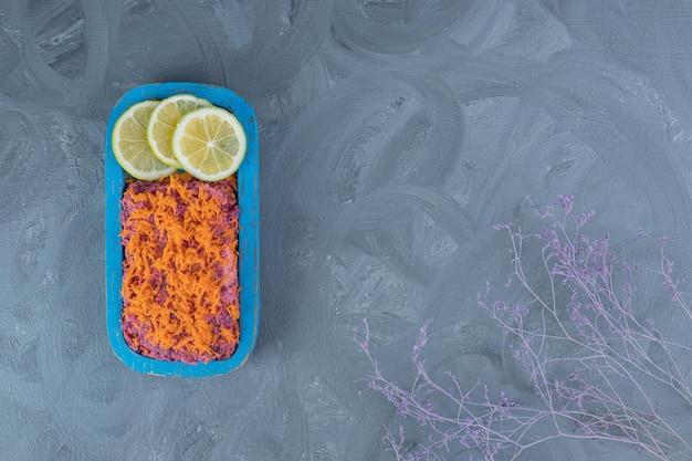 Салат из свеклы и грецких орехов, покрытый морковью и украшенный дольками лимона на мраморном столе.