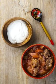 サワークリームと木製のテーブルトップビューに描かれたスプーンと赤いボウルのビートルートキャベツスープ