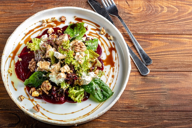 Beetroot carpaccio with walnuts, goat cheese, lettuce and spinach. dressed with sauce. on a dark background.