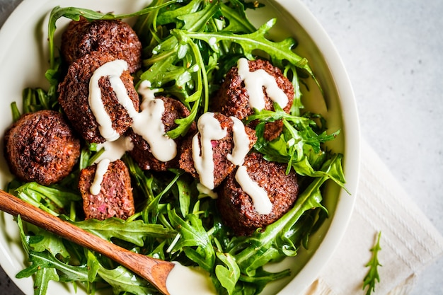 Beetroot falafel with tahini dressing and arugula in a white bowl, top view. healthy vegan food concept.