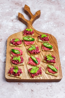 Beetroot hummus canapes withgreen pepper slices and parsley on cutting board on light surface
