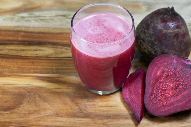 Beetroot juice in clear glass and fresh beetroot on wooden background.