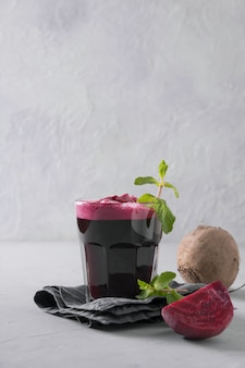 Beetroot juice garnish in glass mint on grey. close up. vertical orientation.