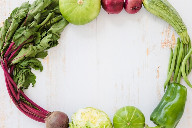 Beetroot leaves; cabbage; gourd; onion; zucchini; green beans and bell pepper on white wooden desk