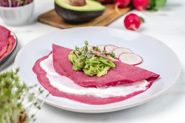 Beetroot pancakes served on plate with avocado