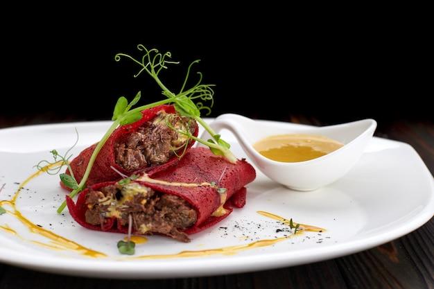 Блинчики из свеклы с мясом, на белой тарелке, на деревянной доске