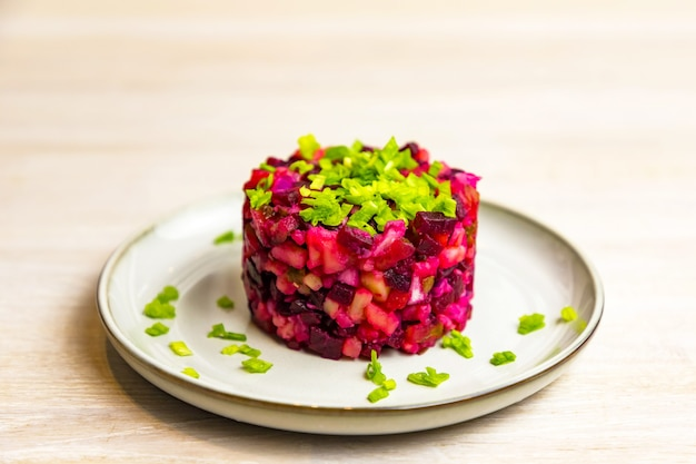 Beetroot russian salad of boiled vegetables in grey white plate on white table background. close up. selective focus. copy space