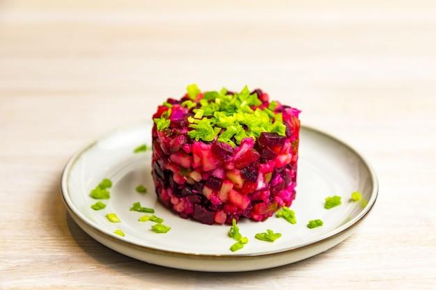 白いテーブルの背景に灰色の白いプレートでゆで野菜のビートルートロシア風サラダ。閉じる。セレクティブフォーカス。コピースペース