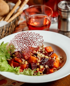 Beetroot salad with carrots, corn and nuts in a white plate