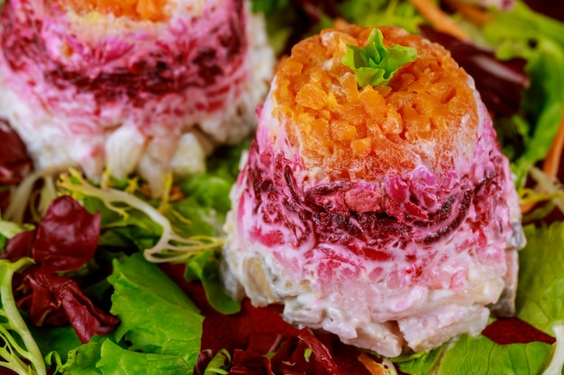 Beetroot salad with herring and vegetable layered with mayonnaise
