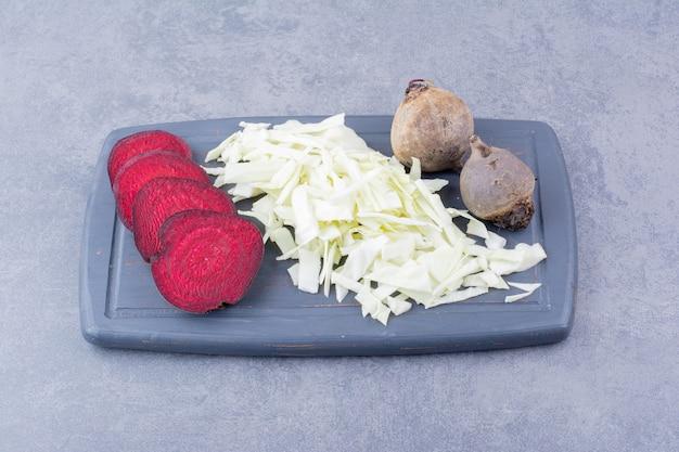 Ломтики свеклы и нарезанная капуста на деревянном блюде