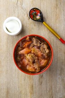 サワークリームと木製のテーブルフラットレイに塗られたスプーンと赤いボウルのビートルートスープ