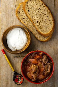 真上の木製のテーブルにサワークリーム、パン、塗装スプーンを添えた赤いボウルのビートルートスープ