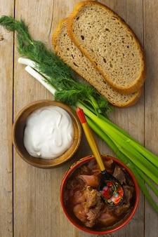素朴なテーブルフラットレイに木のスプーンと赤いボウルのビートルートスープ