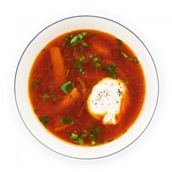 ビートルートスープ-伝統的なウクライナまたはロシアのボルシチと白いボウルにサワークリーム。