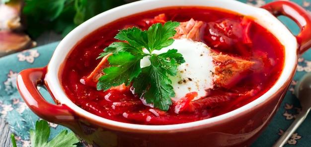 오래된 나무 배경에 있는 갈색 세라믹 그릇에 고기, 사워 크림, 파슬리를 넣은 비트 수프. borsch- 우크라이나 요리의 전통 요리. 선택적 초점입니다.