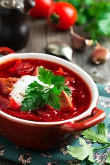 Свекольный суп с мясом, сметаной и петрушкой в коричневой керамической миске