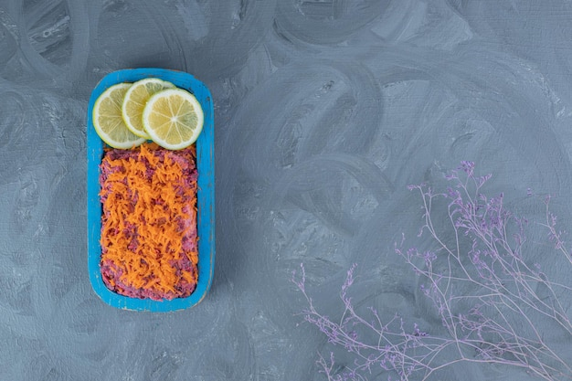 Beetroot and walnut salad topped with carrot and garnished with lemon slices on marble table.