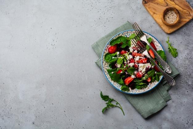 Свекла, клубника, сыр фета и салат из рукколы в керамической тарелке на старой бетонной поверхности стола. вид сверху.