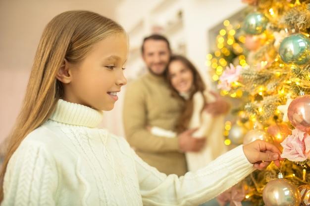 クリスマスの前に。彼の妻と娘が彼を見ている間、お父さんはクリスマスツリーにボールを置きます