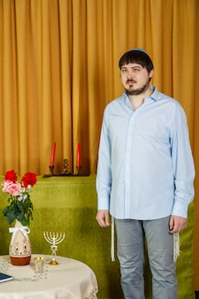 Before the chuppah ceremony, the jewish groom in the synagogue is worried in anticipation of the bride. vertical photo