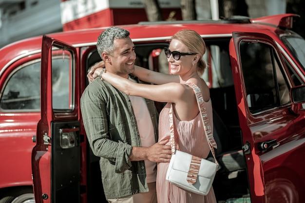 운전하기 전에. 사랑하는 부부는 문이 열린 빨간 복고풍 자동차 근처에서 웃고 서로 껴안고 있습니다.