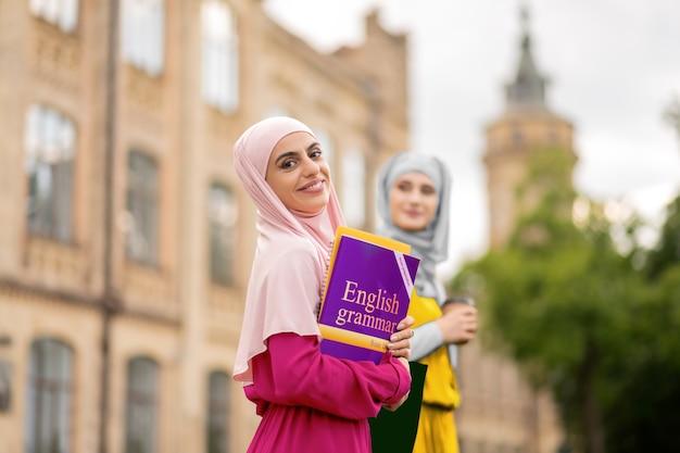 영어 수업 전에. 친구와 함께 걷는 동안 영어 전에 흥분을 느끼는 이슬람 학생