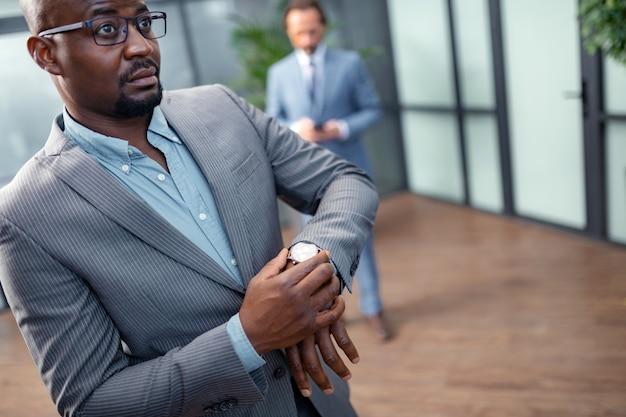 Перед важной встречей. темноглазый бизнесмен в очках обеспокоен перед важной встречей
