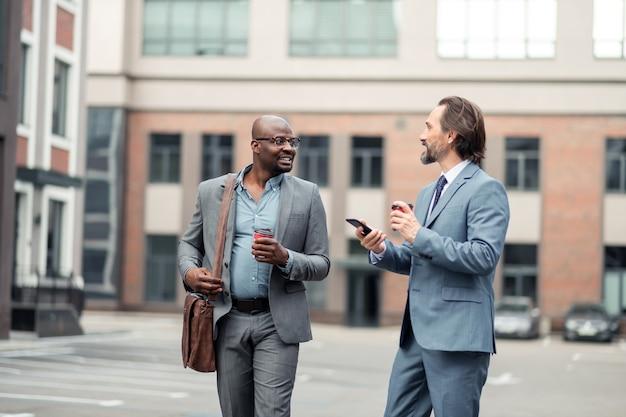 朝の会議の前に。コーヒーを飲みながら朝の会議の前に興奮している繁栄している男性