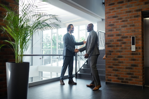 Before the negotiation. two business partners shaking hands and speaking before the negotiation