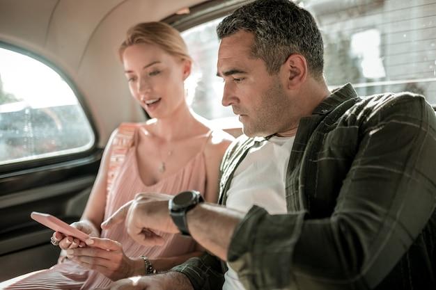 날짜 전에. 놀란 아내가 차를 타고 가는 곳을 보여주는 스마트폰을 가리키는 진지한 남자.