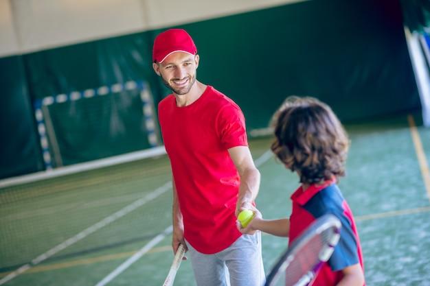 ゲームの前に。テニスをする前に黒髪の少年と握手する赤い帽子の若いひげを生やした男