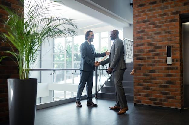Перед переговорами. два деловых партнера пожимают друг другу руки и говорят перед переговорами