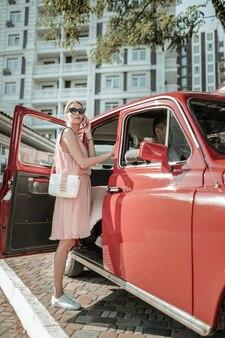 타기 전에. 사려깊은 아름다운 여성이 한 다리를 들고 서 있는 차에 타서 스마트폰을 부릅니다.