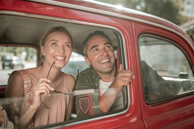 걷기 전. 쾌활한 부부는 차 뒷좌석에 나란히 앉아 창 밖을 내다보고 있습니다.