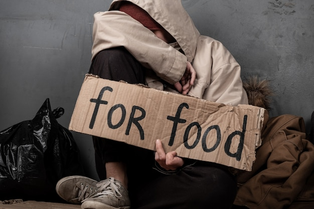 A beggar asks for food with a sign for help.