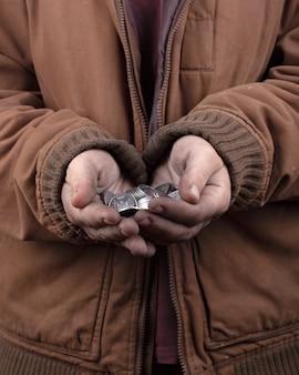 B食のコンセプト。助けを求めるホームレスの人の手を伸ばした。ヤシの木のクローズアップの銀貨