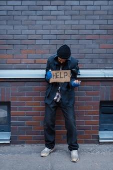 乞食の男と街の通りにサインするのを手伝ってください。